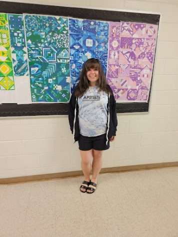 (Picture of Mrs. Reints wearing the new art club shirts)